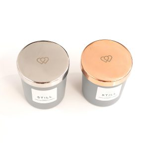 Luxury engraved rose gold tone and silver 9cl mini candle lids for a STILL positive energy candle supplied by The Universal Soul Company