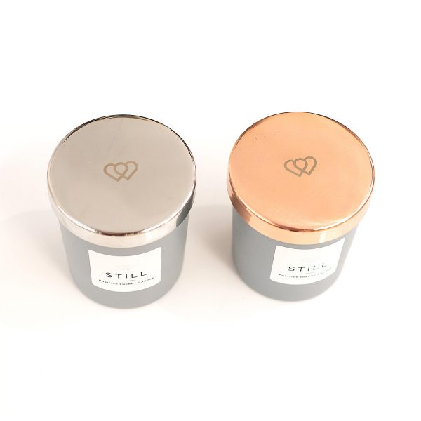 Luxury engraved silver tone and rose gold 9cl candle lids for a STILL positive energy candle supplied by The Universal Soul Company